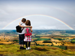 Two children looking at a rainbow.